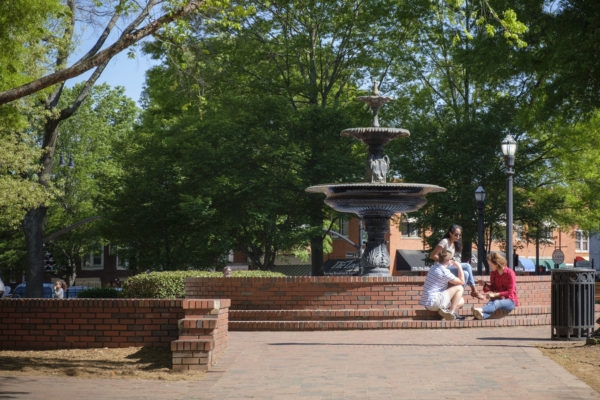 a small group of people sits at the fountain in marietta square