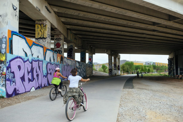 Bikers riding past vibrant grafitti below bridge on beltline