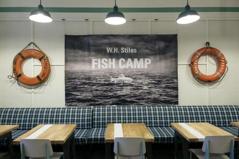 black Fish Camp sign hanging above restaurant booth