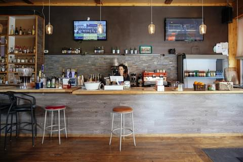 a bar counter with flat screen televisions